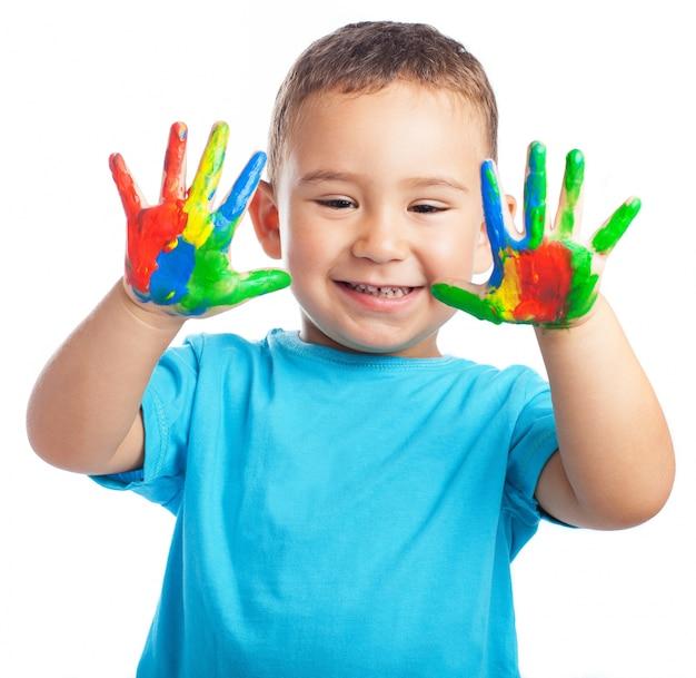 Bambino sorridente con le mani piene di vernice