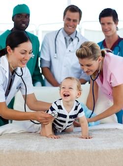 Bambino sorridente con un gruppo di medici in ospedale