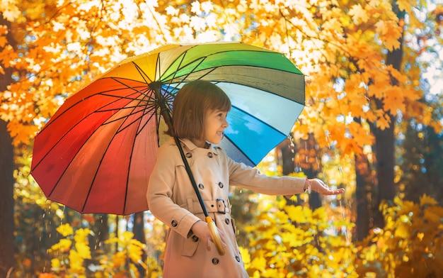 Bambino sotto un ombrello nel parco di autunno. messa a fuoco selettiva.