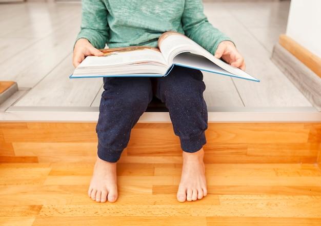 Bambino sta leggendo il libro di carta seduto sulle scale di legno in casa