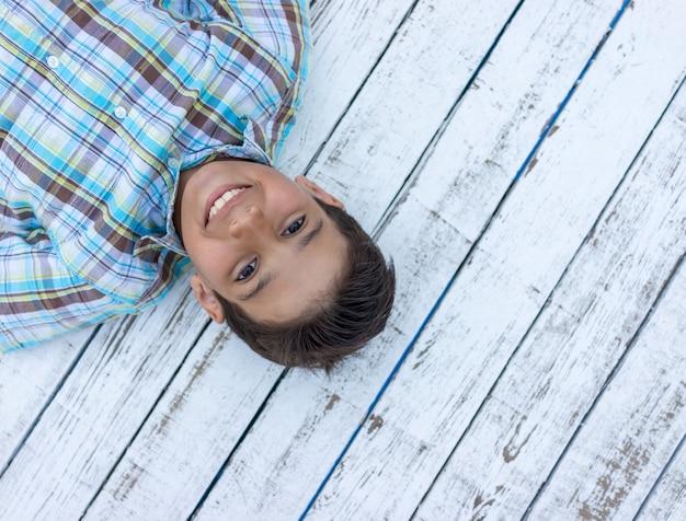 Bambino su fondo di legno bianco