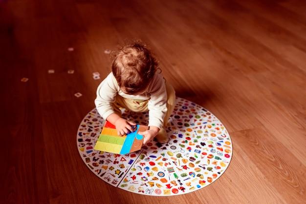 Bambino sul pavimento della sua casa a giocare con un gioco tradizionale.
