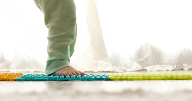 Bambino sul tappetino da massaggio facendo esercizi per la prevenzione del piede piatto