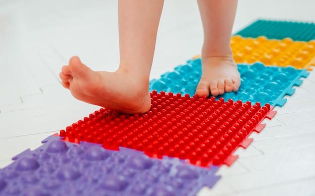 Bambino sul tappetino per massaggio ai piedi del bambino. esercizi per le gambe sul tappeto da massaggio ortopedico. prevenzione dei piedi piatti e dell'alluce valgo