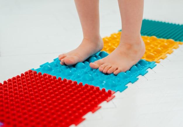 Bambino sul tappetino per massaggio ai piedi del bambino. esercizi per le gambe sul tappeto da massaggio ortopedico.