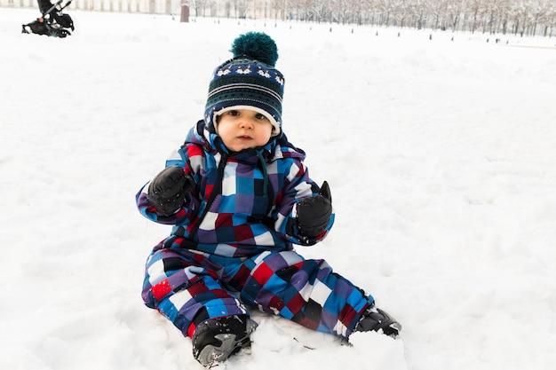 Bambino sulla neve nella foresta