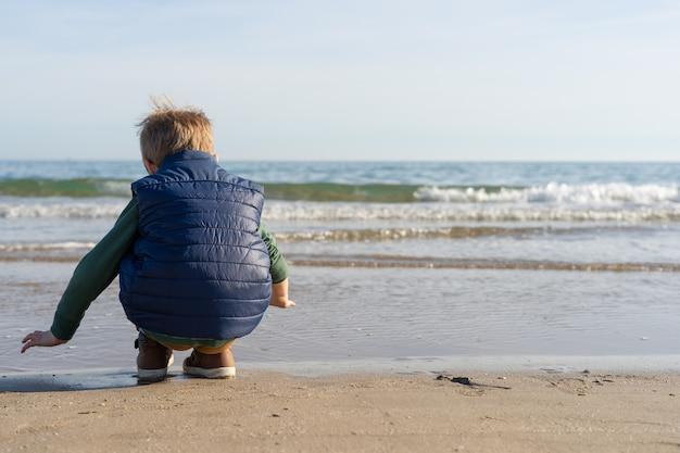 Bambino sulla riva della spiaggia giocando con le onde