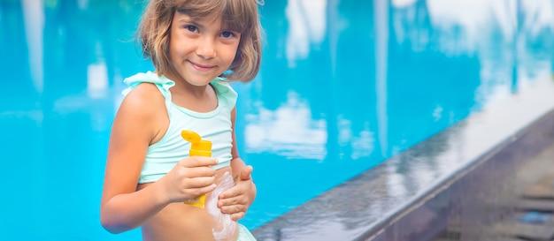 Bambino sulla spiaggia con crema solare sulla schiena