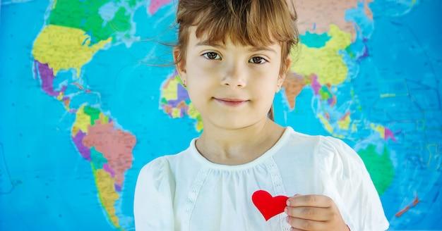 Bambino sullo sfondo della mappa del mondo. ama viaggiare. messa a fuoco selettiva