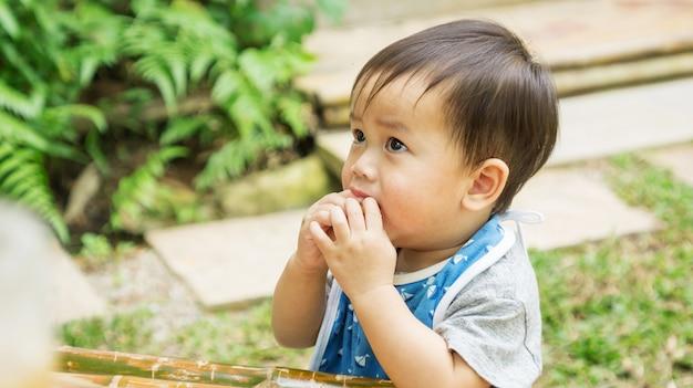 Bambino sveglio asiatico che mangia uno spuntino in un giardino.