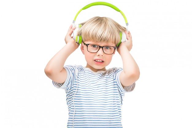 Bambino sveglio che ascolta la musica molto rumorosa che indossa gli auricolari o le cuffie. bambino infelice isolato su fondo bianco che ascolta la radio.