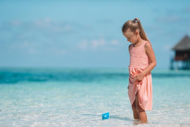 Bambino sveglio che gioca con le barche di carta in un mare