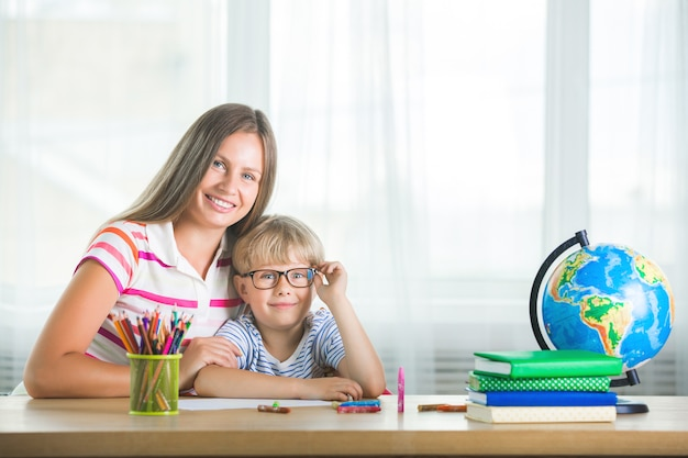 Bambino sveglio che impara una lezione con sua madre. famiglia facendo i compiti insieme. mothe spiega al suo piccolo scolaretto come svolgere un compito.