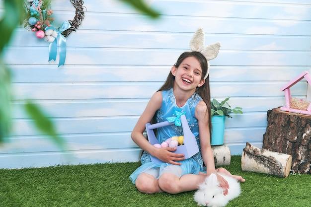 Bambino sveglio che indossa le orecchie del coniglietto il giorno di pasqua. cesto di uova colorate.