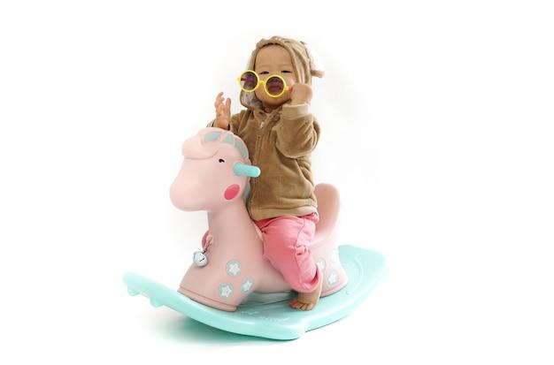 Bambino sveglio che monta un cavallo di legno su bianco