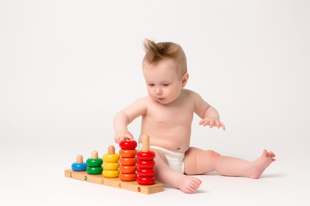 Bambino sveglio con il giocattolo inerente allo sviluppo su una priorità bassa bianca