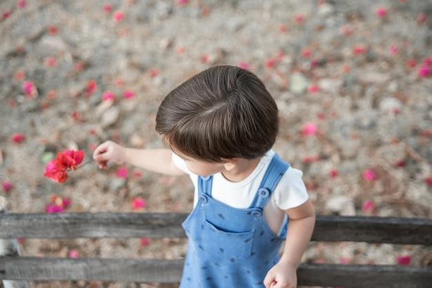 Bambino sveglio del neonato con il pagliaccetto nel giardino sul fiore della tenuta del banco