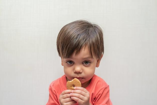 Bambino sveglio del neonato - mangiando il biscotto del wafer