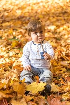 Bambino sveglio della foto a figura intera che gioca con il bastone