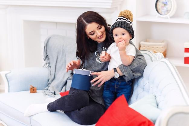 Bambino sveglio divertendosi con sua madre sul comodo sofà blu nella stanza decorata festiva di natale. felice concetto di vacanze invernali.