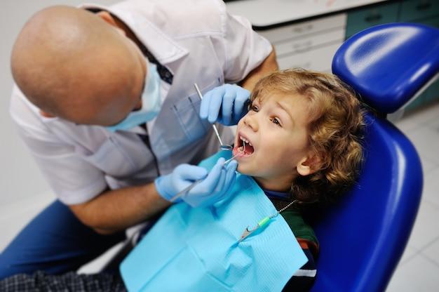Bambino sveglio in un maglione a strisce alla reception dal dentista