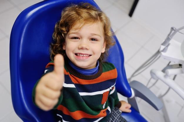 Bambino sveglio in un maglione a strisce alla reception presso il dentista con il pollice in alto