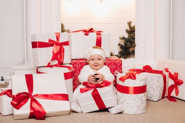 Bambino sveglio in vestito bianco che posa sotto l'albero di natale.