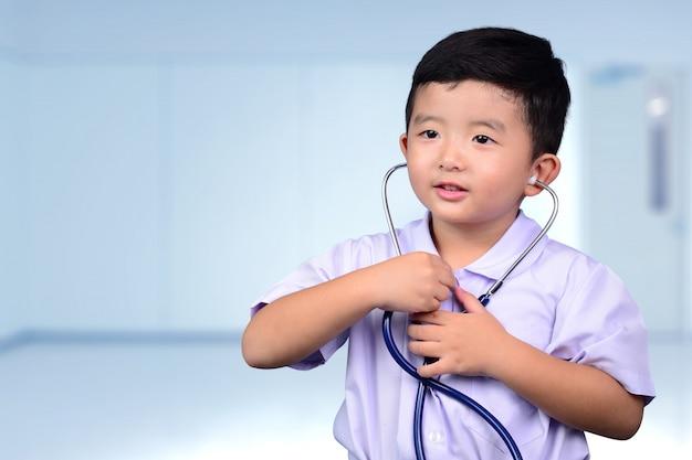 Bambino tailandese asiatico con lo stetoscopio medico