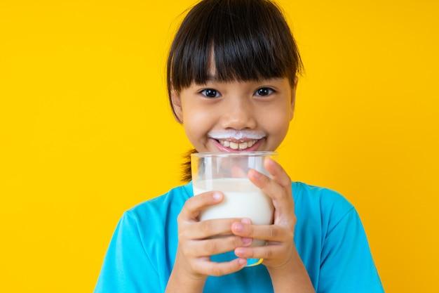 Bambino tailandese felice che giudica il latte alimentare isolato e giovane della ragazza asiatica del bicchiere di latte per forte salute su giallo