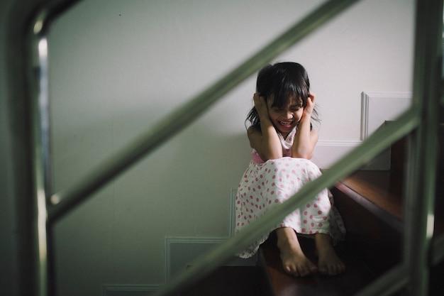 Bambino triste da questo padre e madre che discutono, concetto negativo della famiglia. colore d'annata