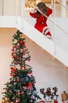 Bambino vestito come santa andando di sotto per i regali di natale
