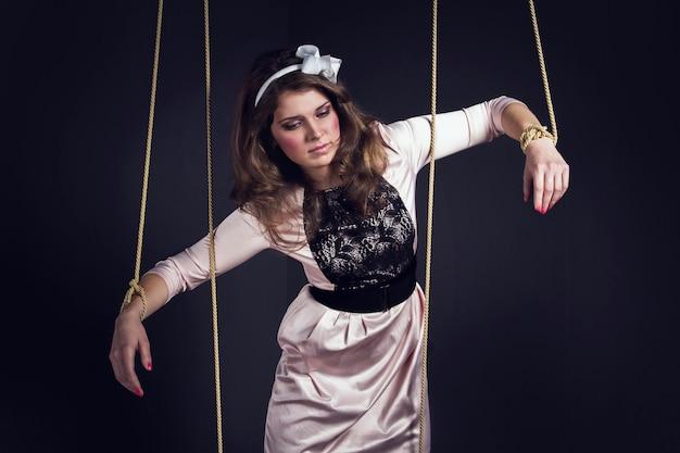Bambola del burattino della donna di halloween su una corda da bucato. bambola ragazza legata con le corde con mani e piedi
