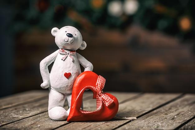 Bambola dell'orso bianco con cuore che sta sul vecchio fondo di legno. concetto di san valentino.
