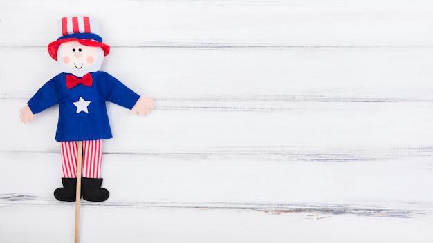 Bambola della bandierina del quarto di luglio su superficie di legno bianca