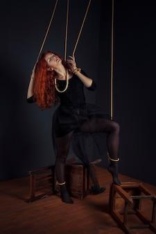 Bambola della marionetta della donna della testarossa di halloween legata con le corde. bambola ragazza legata con le corde con mani e piedi