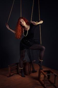Bambola della marionetta della donna della testarossa di halloween legata con le corde. bambola ragazza legata con le corde