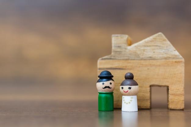Bambola di legno con la faccia felice su fondo di legno