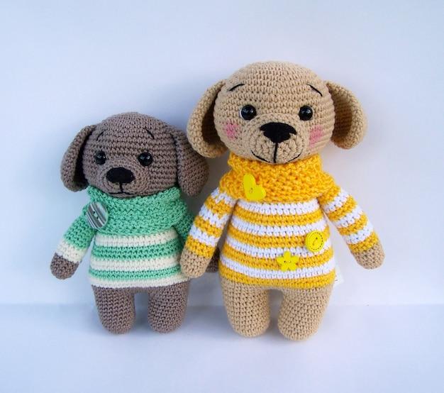 Bambola doggy lavorata a mano sveglia del crochet isolata su fondo bianco con la riflessione dell'ombra.