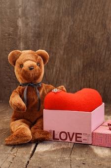 Bambola orso giocattolo e anello gioiello con cuore rosso.