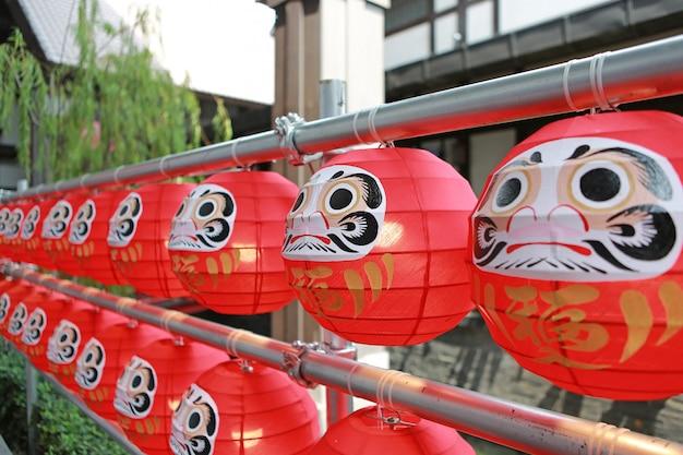 Bambole daruma. le fortunate bambole simboliche giapponesi appese in fila.