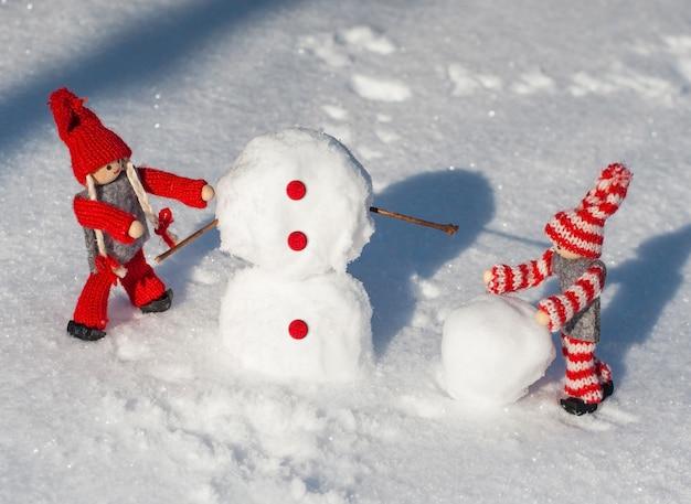 Bambole di legno in abiti di maglia rossa rotolano giù palle di neve per costruire un pupazzo di neve