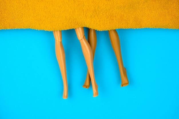 Bambole di plastica di vista superiore sotto la coperta arancio su un fondo blu, concetto del sesso