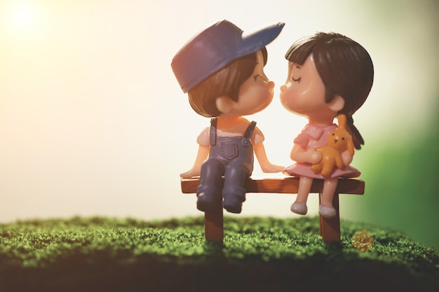 Bambole di ragazzi e ragazze sedersi in panchina