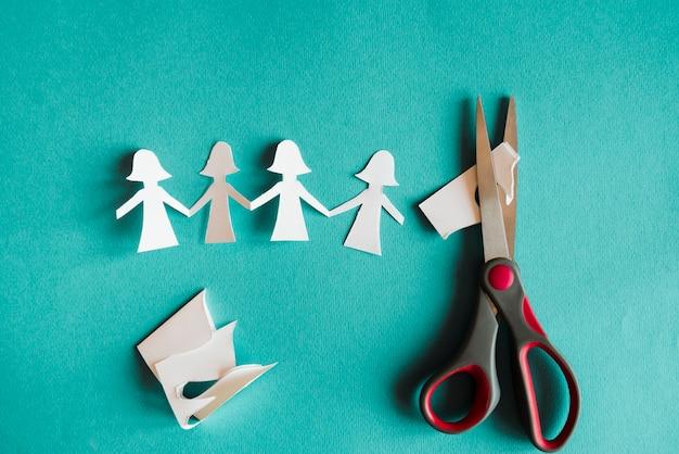 Bambole e forbici tagliate di carta