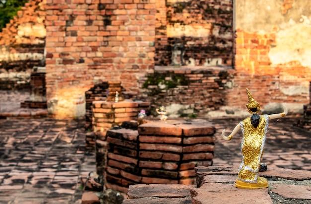 Bambole tailandesi vestono i mattoni del pavimento in un tempio abbandonato.