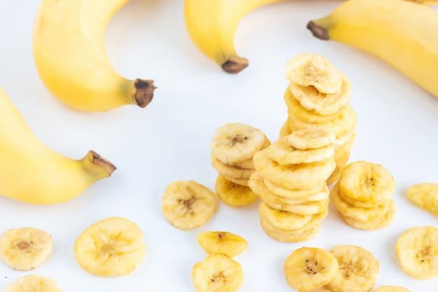 Banana con il mucchio delle fette secche della banana isolate su bianco