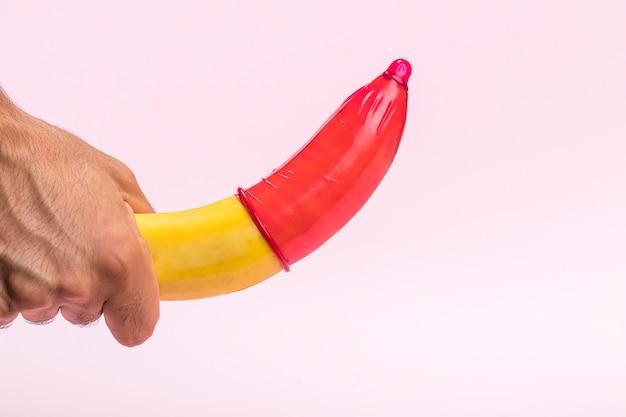 Banana del primo piano con il preservativo rosso su