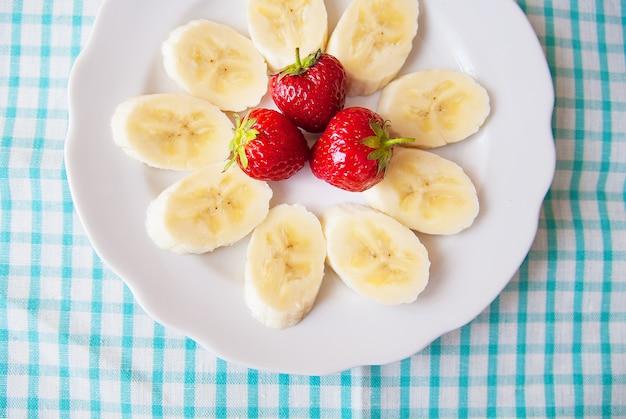 Banana e fragole su un piatto bianco e un tovagliolo colorato.