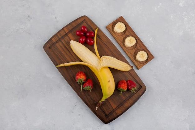 Banana, fragola e frutti di bosco su un piatto di legno al centro