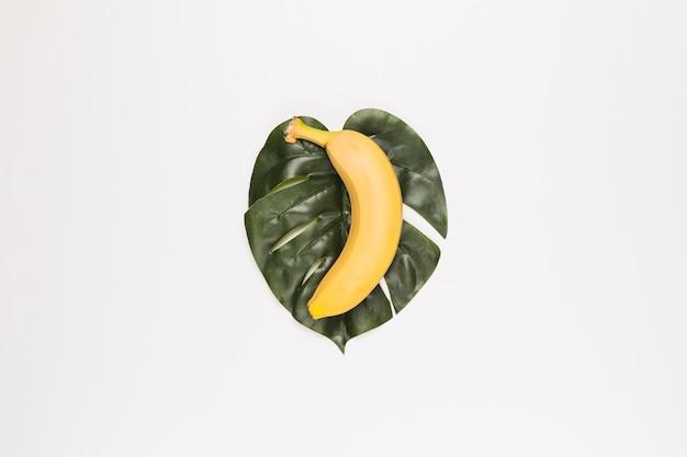 Banana gialla sulla foglia verde nel centro della superficie bianca
